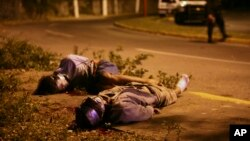 FILE - Bodies of two victims of Mexico's ongoing drug war are seen lying by the side of a road as police secure the area in the city of Veracruz, Mexico.