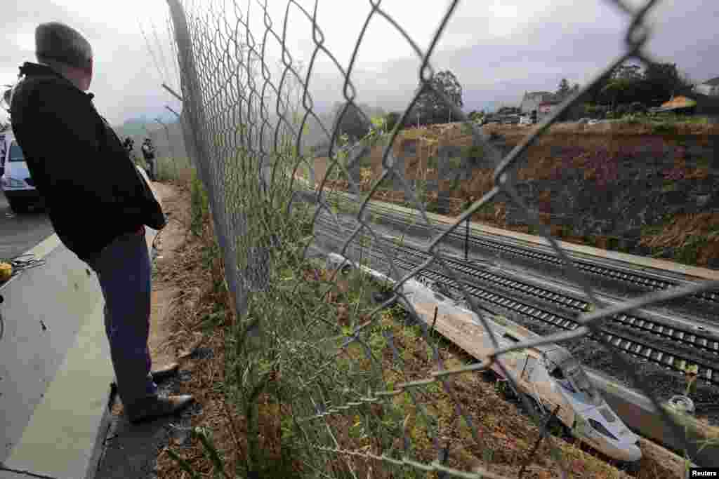 A man looks at the train engine at the site of a crash that killed at least 80 people Wednesday in Santiago de Compostela, northwestern Spain.
