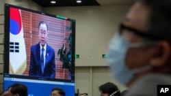 ທ່ານຫວາງ ຢີ (ກາງ), ລັດຖະມົນຕີກະຊວງການຕ່າງປະເທດຈີນ ແລະພວກເຂົ້າຮ່ວມກອງປະຊຸມໃສ່ໜ້າກາກປິດປາກໄວ້ ເພື່ອຫລຸດຜ່ອນການແຜ່ລະບາດຂອງໄວຣັສໂຄໂຣນາ ຂະນະທີ່ຟັງການກ່າວຄໍາປາໄສ ຂອງທ່ານ Ban Ki-moon ອະດີດເລຂາທິການໃຫຍ່ອົງການສະຫະປະຊາຊາດທີ່ຖ່າຍທອດທາງໂທລະພາບຢູ່ກອງປະຊຸມສົນທະນາກ່ຽວກັບການຈັດລໍາດັບປະເທດໃນສາກົນ