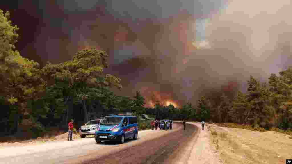 Paramilitary police officers and people watch as a wildfire fanned by strong winds rage near the Mediterranean coastal town of Manavgat, Antalya, Turkey.