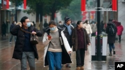 Masked pedestrians walk down a shopping street in downtown Wuhan, China, Wednesday, Jan. 22, 2020. The number of cases of a new coronavirus from Wuhan has risen over 400 in China and the death toll to 9, Chinese health authorities said.