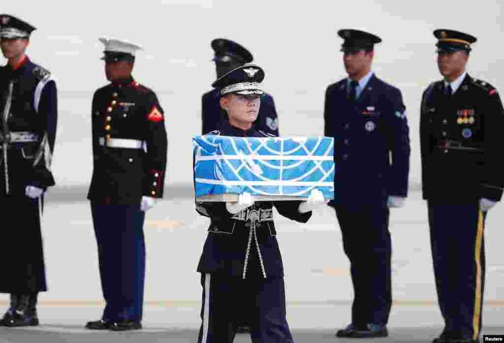 Kore Savaşı'nda ölen ve Kuzey Kore'nin yeni iade ettiği Amerikan askerlerinden birinin cenazesinden kalanlar BM bayrağına sarılı bir kutuda Güney Koreli bir asker tarafından taşınıyor. Fotoğraf Güney Kore'deki Osan Hava Üssü'nde çekilmiş.
