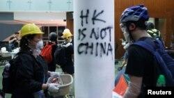 Beberapa demonstran Hong Kong tampak menyerbu gedung badan legislatif kota itu hari Senin malam (1/7).