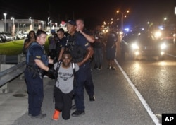 Police arrest Black Lives Matter leader DeRay McKesson during a protest along Airline Highway, a major road that passes in front of the Baton Rouge Police Department headquarters, July 9, 2016, in Baton Rouge, Louisiana.