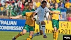 Pemain Australia Vincenzo Grella (kiri) dan bintang tim Amerika, Landon Donovan (kanan) berebut bola dalam pertandingan pemanasan Piala Dunia di Roodenpoort, Johannesburg, Afrika Selatan, Sabtu, 5 Juni 2010. Tim Amerika mengalahkan Australia 3-1.