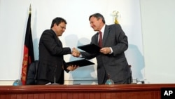 Afghan Finance Minister Omar Zakhilwal and U.S. Ambassador to Afghanistan Karl Eikenberry sign the debt relief agreement in Kabul.