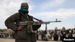 Seorang anggota Taliban dan warga lainnya berkumpul di lokasi eksekusi tiga pria di provinsi Ghazni, Afghanistan (18/4).