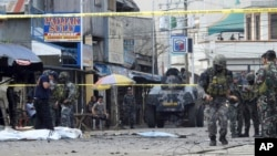 Police investigators and soldiers attend the scene after two bombs exploded outside a Roman Catholic cathedral in Jolo, the capital of Sulu province in southern Philippines, Jan. 27, 2019.