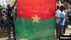 Warga melakukan unjuk rasa anti-kudeta dengan membentangkan bendera nasional Burkina Faso di ibukota Ouagadougou, Selasa (22/9).