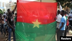 Anti-coup protesters hold Burkina Faso flag in Ouagadougou, Sept. 22, 2015.