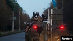 乌克兰政府军士兵坐在装甲车顶前往乌东一处军事基地。(2014年8月19日)