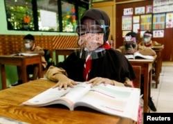 Siswa sekolah dasar yang mengenakan masker dan pelindung wajah menghadiri kelas, saat sekolah dibuka kembali di tengah pandemi penyakit virus corona (COVID-19), di Jakarta, 7 April 2021. (Foto: Reuters)