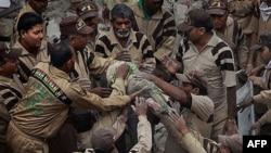 Nhân viên cứu hộ kéo thi thể một nạn nhân ra khỏi đống đổ nát của tòa nhà cao tầng bị sập ở New Delhi, ngày 16/11/2010