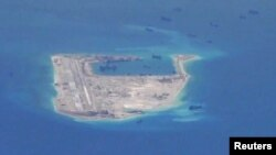 Chinese dredging vessels are purportedly seen in the waters around Fiery Cross Reef in the disputed Spratly Islands in the South China Sea in this still image taken by a P-8A Poseidon surveillance aircraft, May 21, 2015.