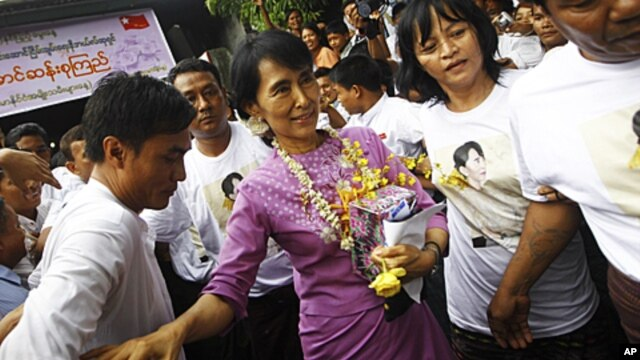 Pro-democracy leader Aung San Suu Kyi (C) holds her birthday gift as she makes her way through the crowd gathered at her National League for Democracy headquarters in Rangoon, June 19, 2011.