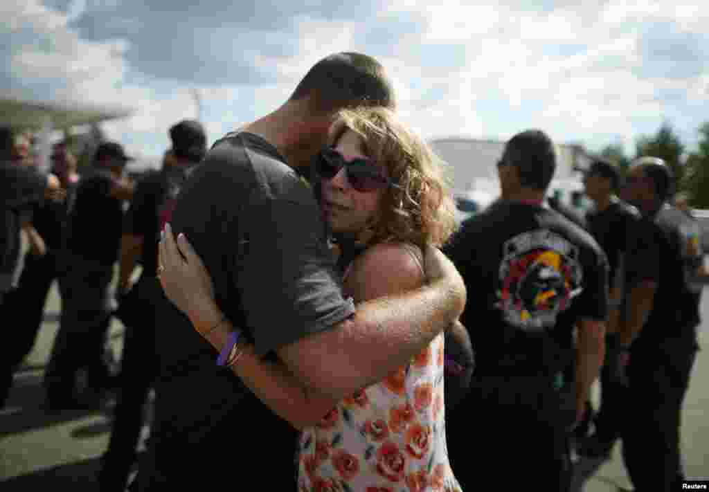 Anna Woyjeck, the mother of fallen firefighter Kevin Woyjeck, hugs a firefighter in front of a memorial dedicated to the 19 firefighters killed in the nearby wildfire in Prescott, Arizona, July 8, 2013.