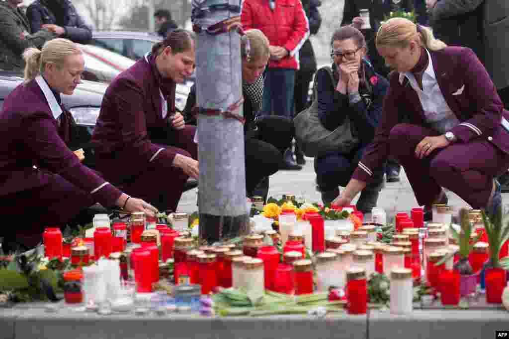 Employees of German airline Germanwings lay down candles and flowers for the victims of the plane crash in front of the company's headquarters in Cologne, western Germany. a Germanwings Airbus A320 coming from Barcelona and heading to Duesseldorf smashed into the French Alps, killing all 150 people on board.