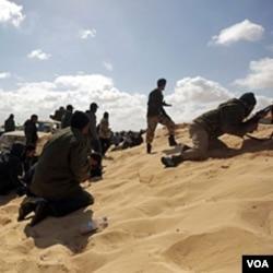 Para pemberontak Libya mencari perlindungan dalam bentrokan dengan pasukan pro-Gaddafi di kota Ajdabiya (21/3).