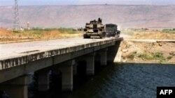 Сирийский танк пересекает мост через реку аль Асси