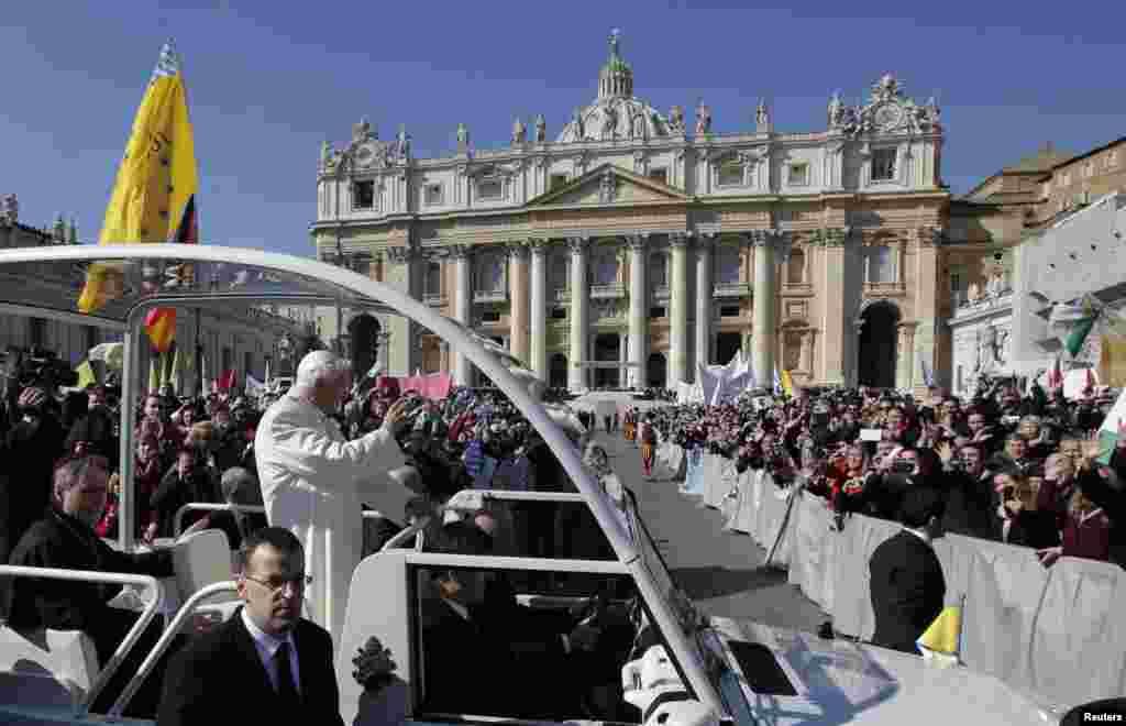 教宗本笃16世2013年2月27日抵达梵蒂冈圣彼得广场举行最后一次公开接见信众活动时,向信众挥手。