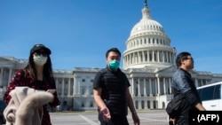 Pemandu wisata mengenakan masker, memandu sekelompok turis di Gedung Capitol, Washington DC, 9 Maret 2020.