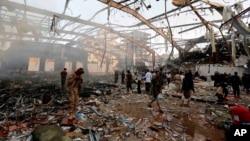 Warga Yaman memeriksa bekas serangan udara koalisi pimpinan Saudi yang menghantam warga yang menghadiri upacara pemakaman di Sanaa, Yemen (8/10). Yaman yang dikoyak perang sedang menghadapi ancaman wabah kolera.