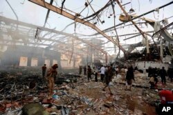 People inspect the aftermath of a Saudi-led coalition airstrike in Sanaa, Yemen, Oct. 8, 2016.