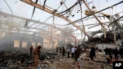 People inspect the aftermath of a Saudi-led coalition airstrike on a funeral in Sana'a, Yemen, Oct. 8, 2016. The coalition on Saturday said its warplanes bombed the wrong target.