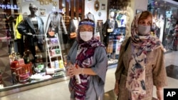 Women wearing protective face masks and gloves to help prevent the spread of the coronavirus shop at the Kourosh Shopping Center in Tehran, Iran, Monday, April 20, 2020.