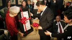 Sarah Lande (L) presents China's Vice President Xi Jinping a reproduction of the Muscatine Journal newspaper from 1985, when he first visited in Muscatine, Iowa, February 15, 2012.