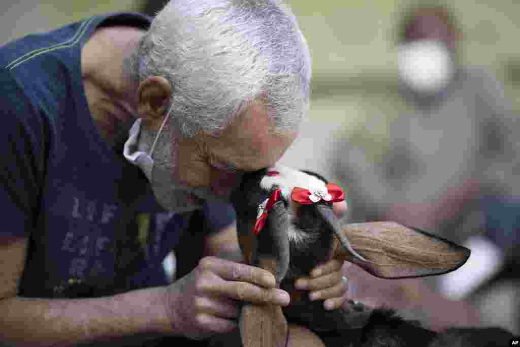 An elderly man caresses a goat named Jurema, wearing ribbons on her ears, at the Maria Vieira Bazani nursing home in Rio de Janeiro, Brazil.