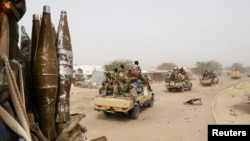 Des soldats tchadiens patrouillent en voiture à travers la ville de Gambaru, Nigeria, le 26 Février 2015.