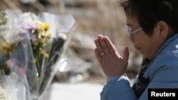 Một phụ nữ cầu nguyện cho các nạn nhân vụ động đất và sóng thần tại thị trấn Namie, tỉnh Fukushima, ngày 11/3/2014.