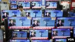 首爾的一名店員觀看電視屏幕上有關北韓核試驗的消息。(2016年1月6日)