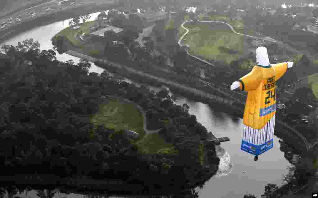 A hot air balloon in the likeness of Brazil's Christ The Redeemer statute, wearing the colors of Australia's soccer team floats over the Melbourne skyline, June 10, 2014. (photo provided by sportsbet.com.au)