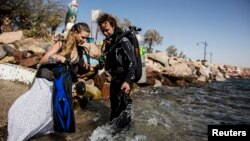 A model (L) enters the water before an underwater photo shoot in the Red Sea in the resort city of Eilat Oct. 23, 2013.