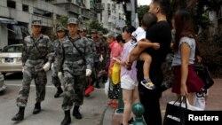 在颱風襲擊澳門後中國軍隊幫助清理完走在澳門街頭。 (2017年8月27日)