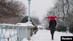 一名婦人在波士頓走過一個鋪滿白雪的公園
