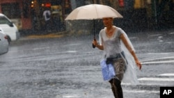 FILE - A woman holding an umbrella crosses a street in heavy rain in Tokyo's Ginza shopping district, Wednesday, Sept. 9, 2015.