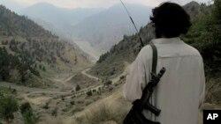Seorang militan Taliban Pakistan melihat ke arah jalan utama Shawal di Waziristan Utara, Pakistan (10/8/2013). Militan Taliban di Pakistan dilaporkan berlatih di negara itu untuk menghadapi perang etnis jika tentara asing ditarik dari Afghanistan akhir 2014.