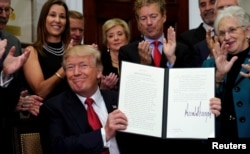 President Donald Trump smiles after signing an executive order to make it easier for Americans to buy bare-bones health insurance plans and circumvent Obamacare rules, at the White House in Washington, Oct. 12, 2017.