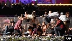 在明显的枪声出现之后,人们试图逃离内华达州拉斯维加斯的户外乡村音乐演唱会现场(2017年10月1日)