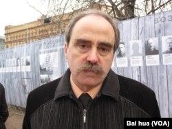 纪念碑人权组织领导人拉钦斯基,他身后的背景是斯大林政治迫害中遭处决人士的画像,以及前克格勃,目前是联邦安全局总部大楼。(美国之音白桦拍摄)