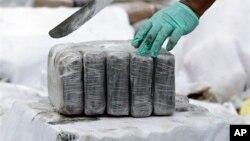 Cảnh sát chống ma túy chuẩn bị cắt khối hàng cocaine. (Ảnh minh họa).