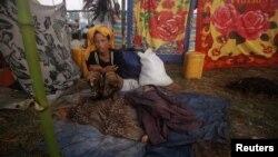 一名因最近若开邦的宗派暴力离乡背井的妇女与她的孩子11月1日在难民营里