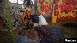 ຍິງອົບພະຍົບຜູ້ນຶ່ງ ນັ່ງໃກ້ກັບລູກຂອງລາວ ທີ່ກໍາລັງນອນຫລັບຢູ່ ຢູ່ໃນສູນອົບພະຍົບ Owntaw ສໍາລັບຊາວມຸສລິມ ທີ່ຕັ້ງຢູ່ນອກເມືອງ Sittwe ເມືອງຫລວງຂອງລັດຣາຄິນ ໃນພາກຕາເວັນຕົກຂອງມຽນມາ, ວັນທີ 1 ພະຈິກ 2012.