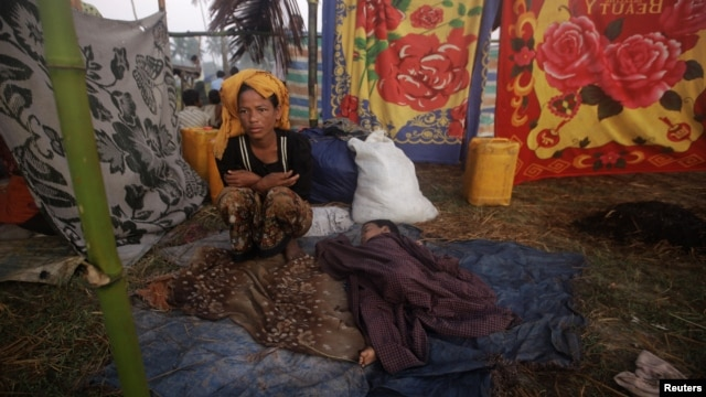 A woman displaced by the recent violence in Pauktaw sits by her sleeping child at Owntaw refugee camp for Muslims outside Sittwe, Burma, November 1, 2012.