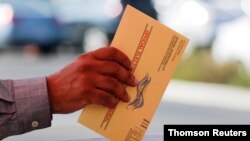 FILE - An election worker places a mail-in ballot into an election box at a drive-through drop-off site at the Registrar of Voters in San Diego, California.