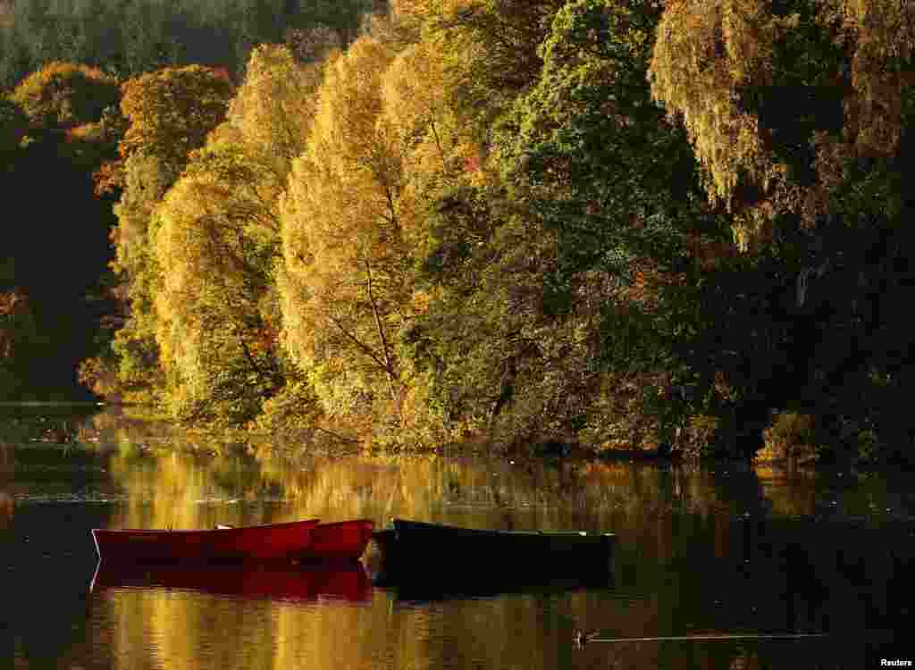 Moored boats are seen on Loch Faskally, as autumn leaves are reflected in the water, in Pitlochry, Scotland.