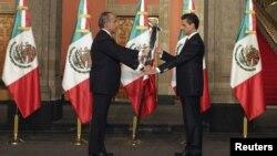Presiden Meksiko Felipe Calderón (kiri) menyerahkan bendera Meksiko kepada Presiden baru Enrique Peña Nieto pada upacara pelantikan di Mexico City (1/12).